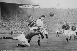 Brown challenges Manchester City keeper Bert Trautmann during the 1956 FA Cup final